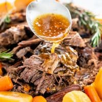 a spoon pouring gravy over the crock pot roast