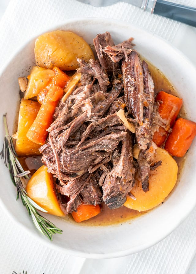 Crock Pot Roast on a white plate with carrots and potatoes