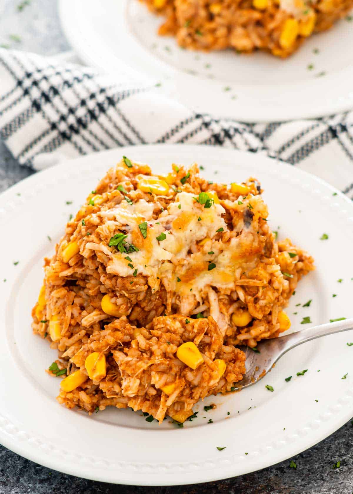 a slice of chicken enchilada rice casserole on a white plate.