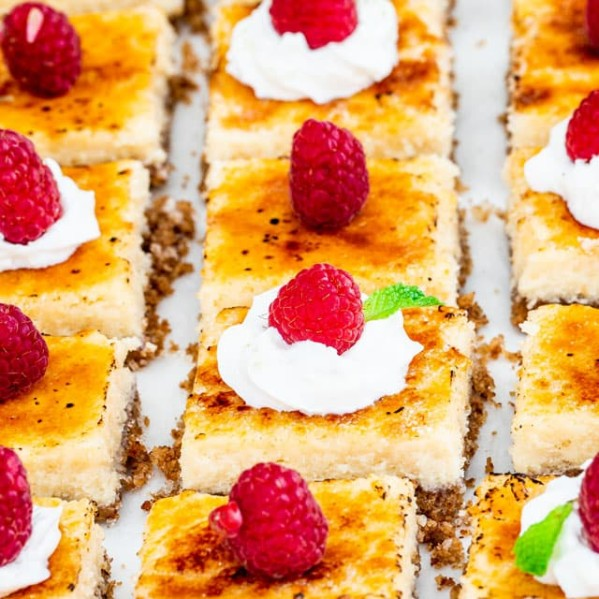 side view shot of creme brulee cheesecake bars topped with whipped cream and raspberries