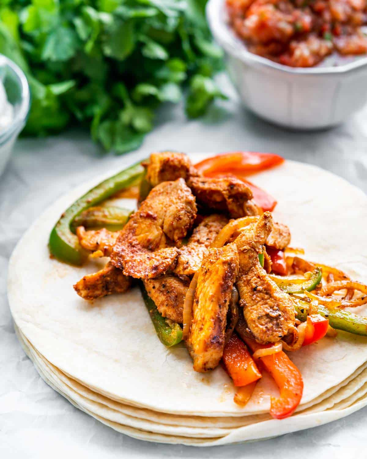 chicken fajitas over a stack of tortillas