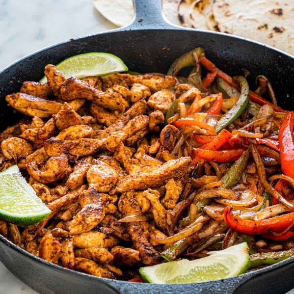 chicken fajitas in a skillet garnished with lime wedges