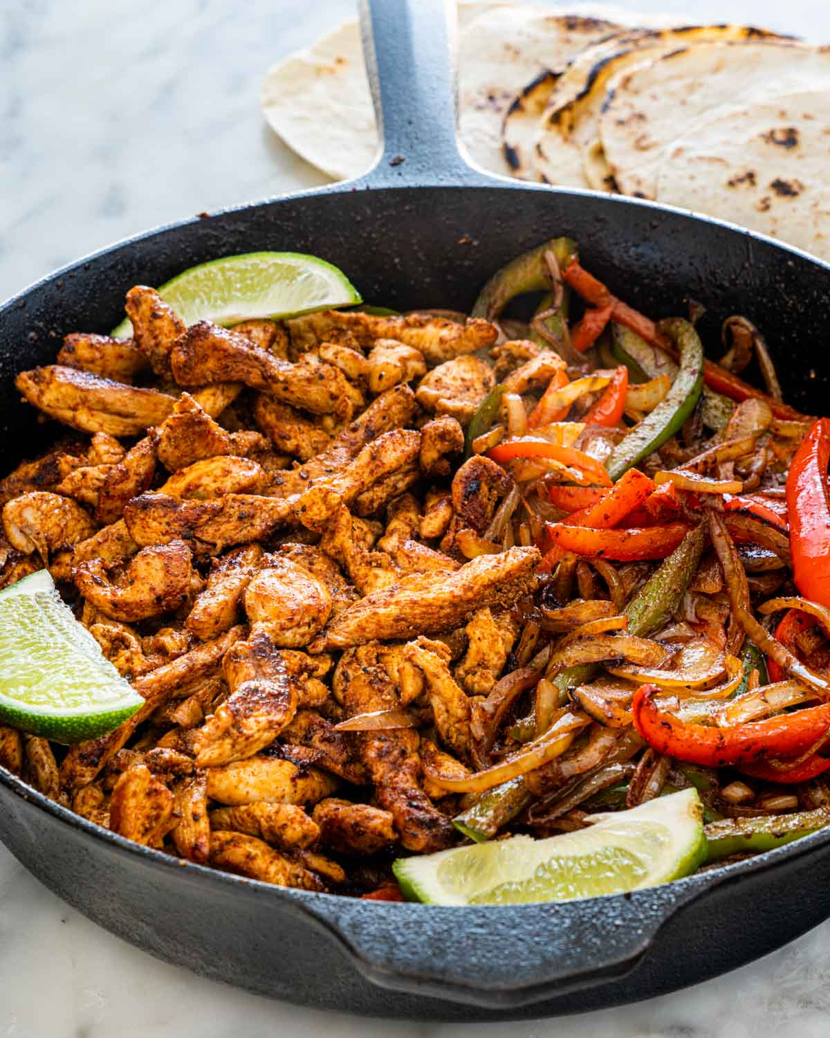 chicken fajitas in a skillet with lime wedges
