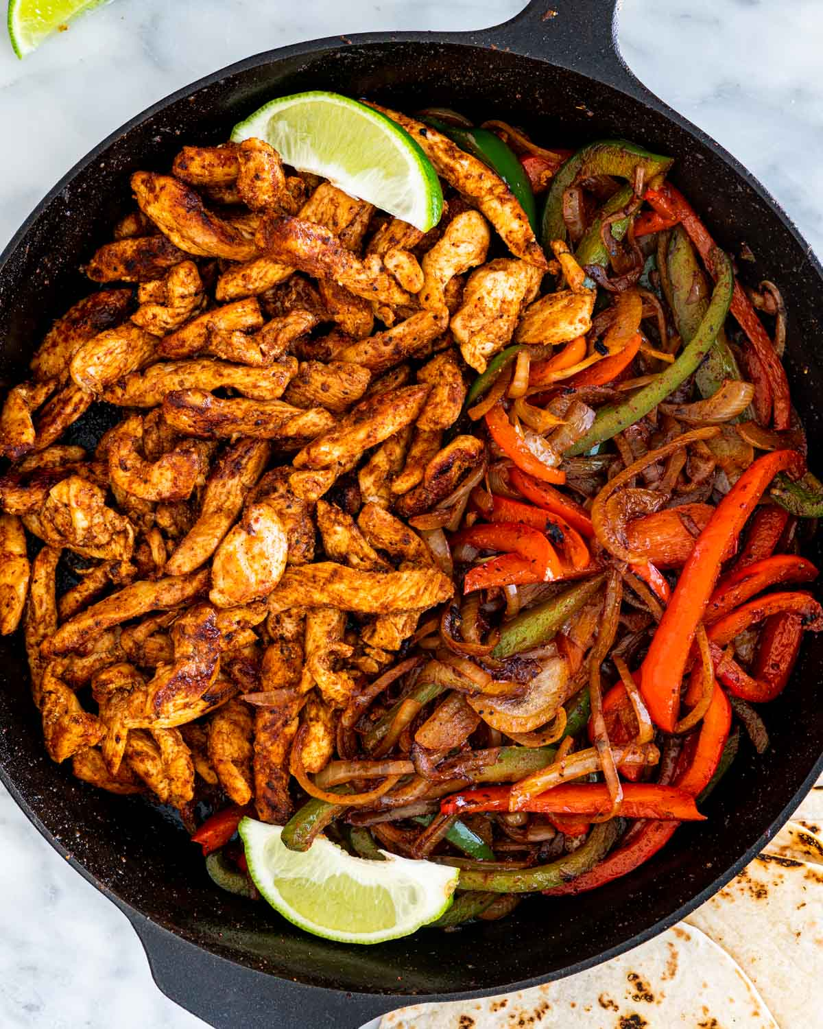 overhead shot of chicken fajitas in a skillet