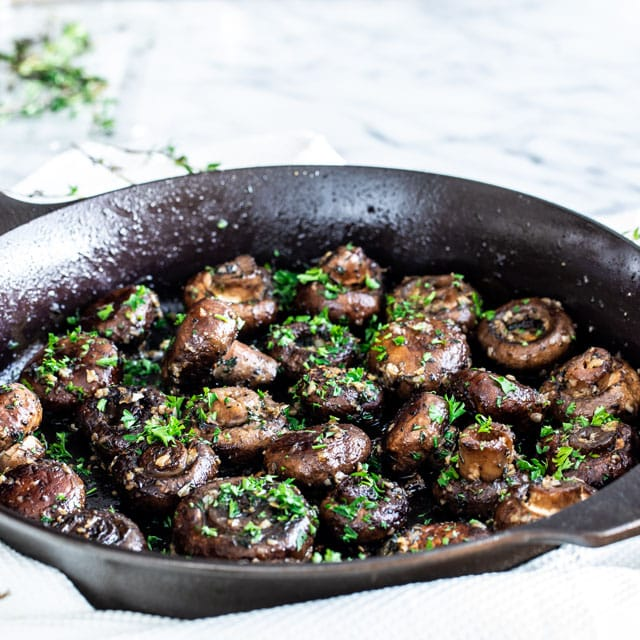 a skillet filled with garlic butter mushrooms topped with parsley