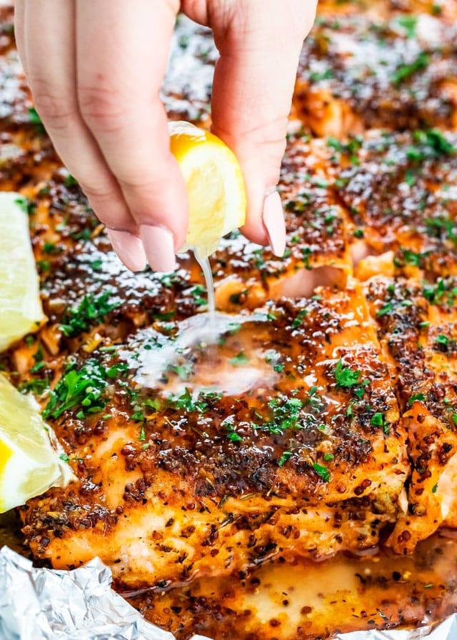 squeezing a lemon wedge over Honey Mustard Salmon