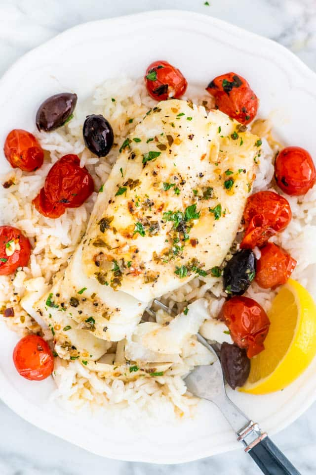Lemon Butter Baked Cod over rice in a white plate