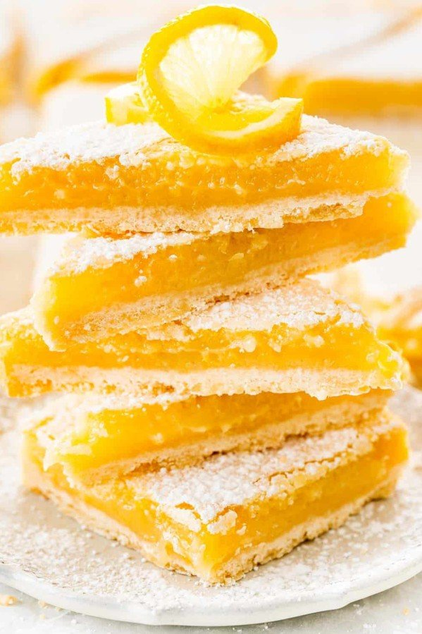 lemon bars cut into triangles stacked on top of each other on a white plate.