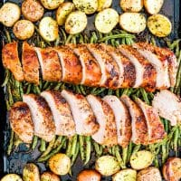 overhead shot of sliced honey mustard pork tenderloin on top of roasted green beans with roasted potatoes on either side