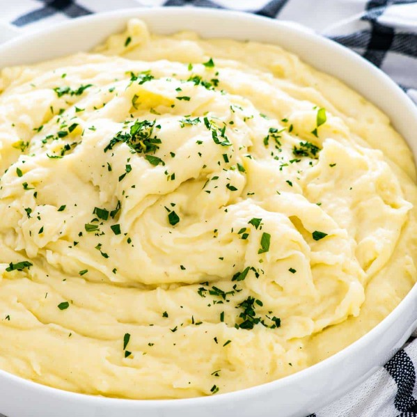 creamy mashed potatoes in a white bowl garnished with parsley.