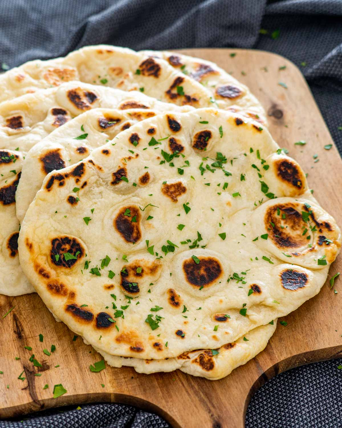 a bunch of naan on a cutting board garnished with parsley.