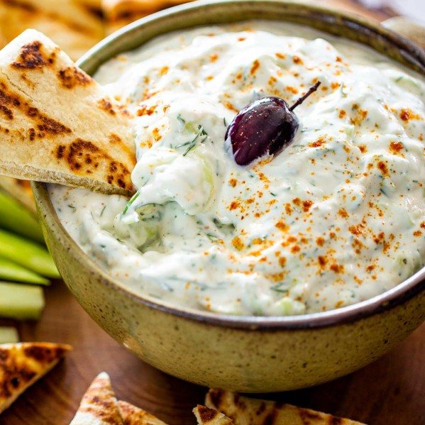 tzatziki sauce in a bowl with an olive on top surrounded by pita chips.