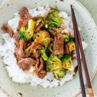 overhead shot of beef and broccoli on a bed of white rice, with chopsticks resting in the bowl