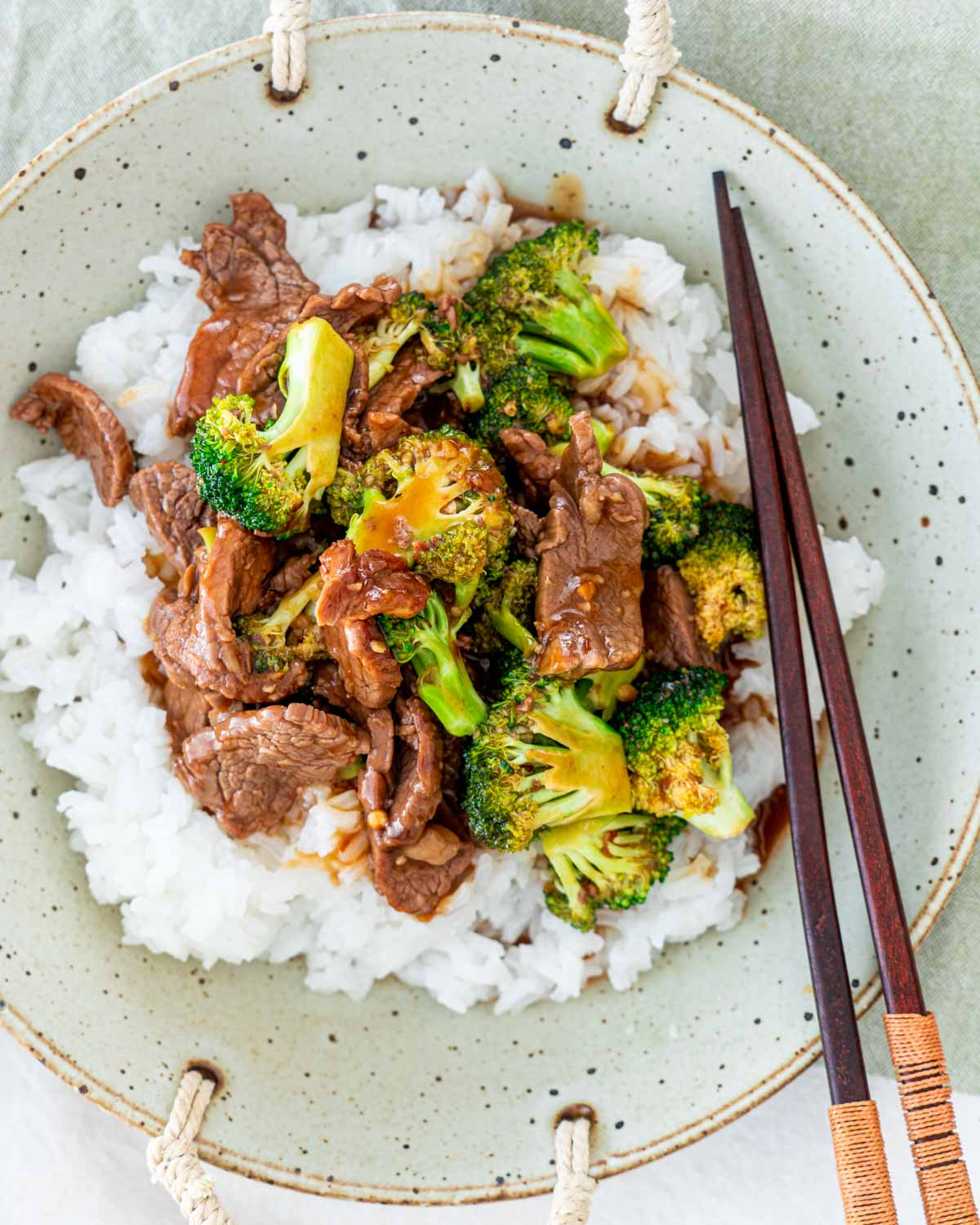 overhead shot of beef and broccoli over a bed of rice in a plate with chopsticks