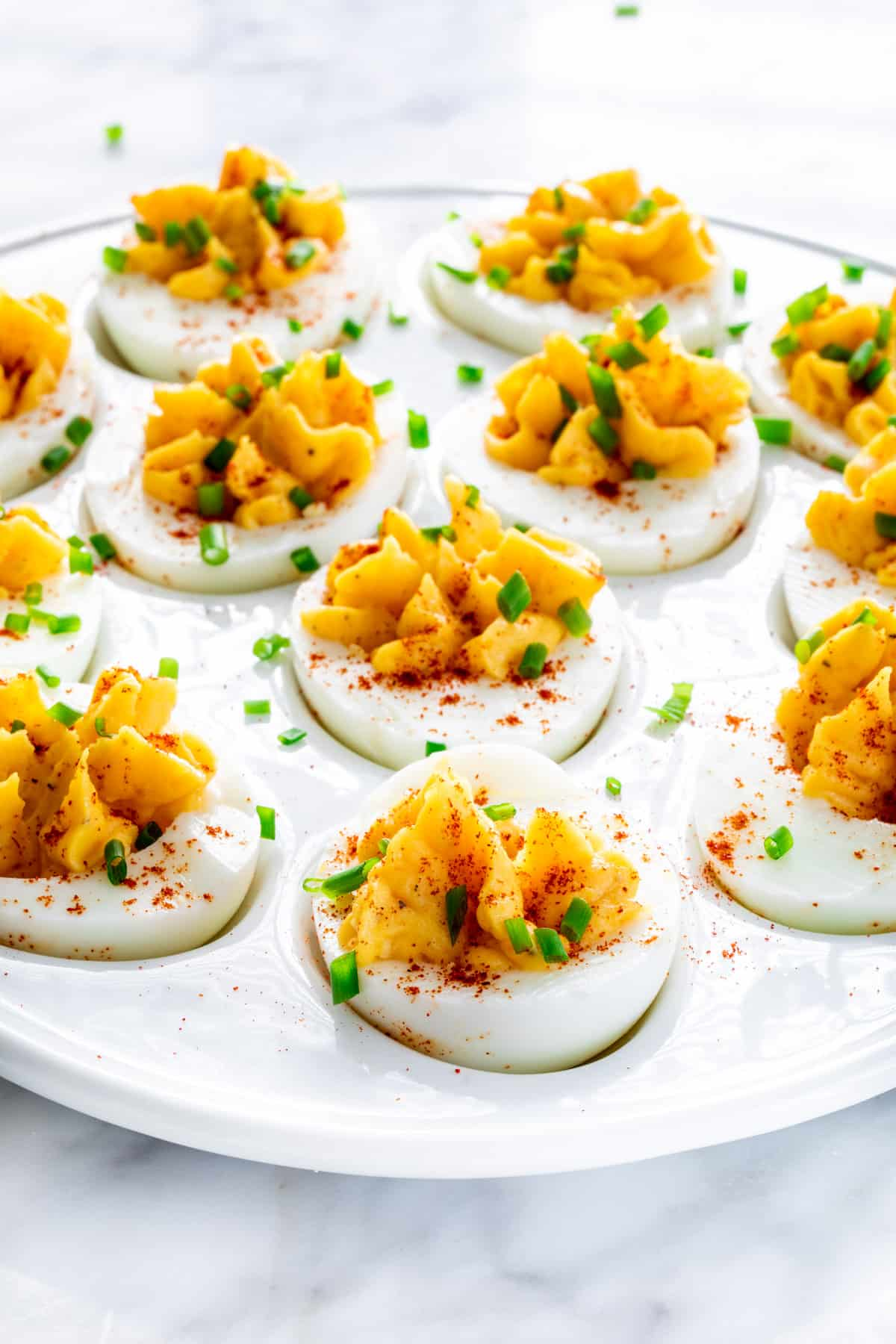 deviled eggs on a platter garnished with paprika and chives