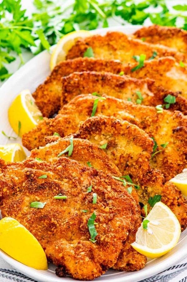 a bunch of pork schnitzel on a serving platter with lemon wedges.