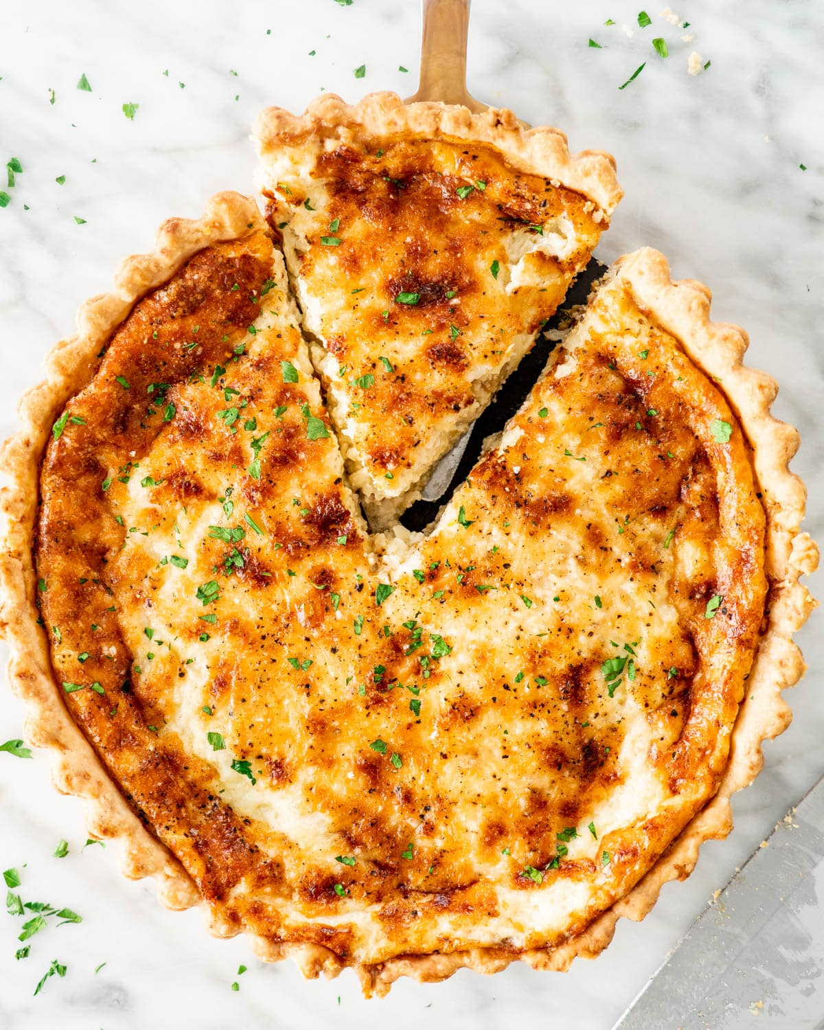 overhead shot of quiche lorraine with a slice coming out of it