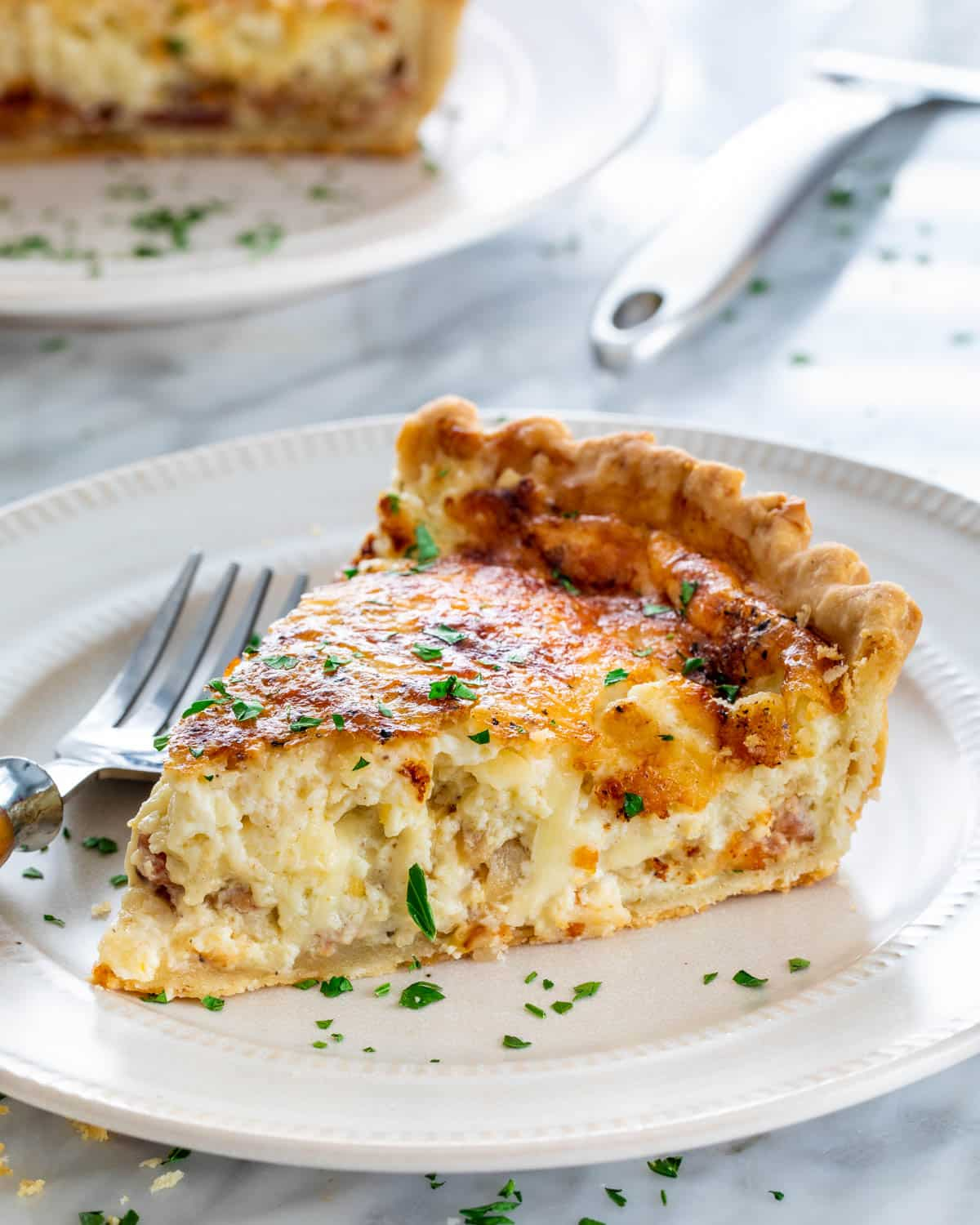 a slice of quiche on a white plate