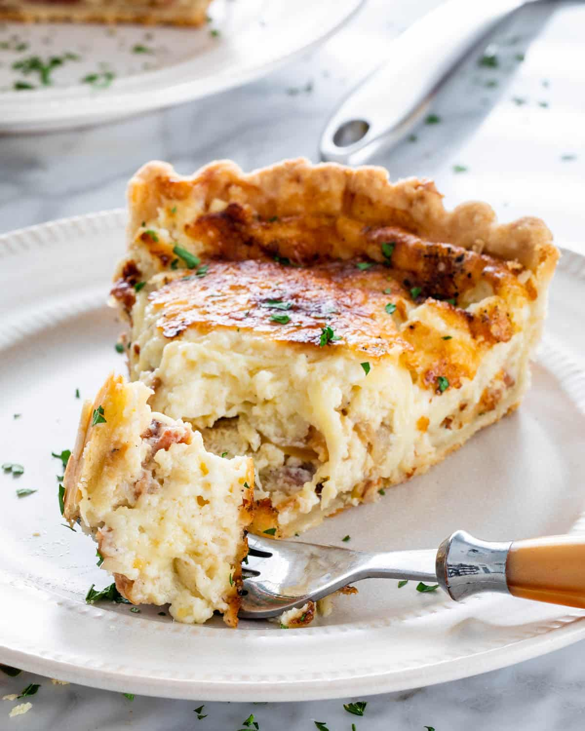 a slice of quiche on a white plate with a fork with a bite taken out of it