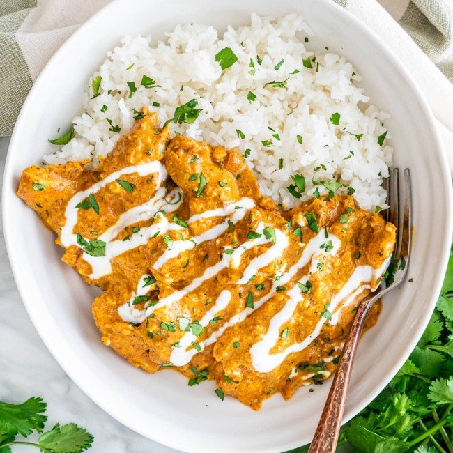 overhead shot of a bowl of chicken korma with a side of rice