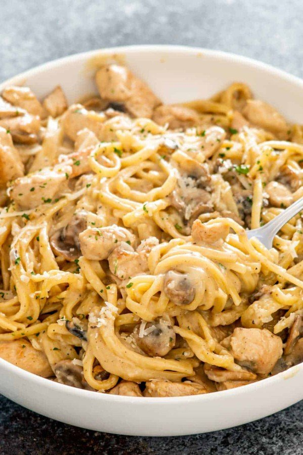 chicken tetrazzini garnished with parmesan cheese in a white bowl.