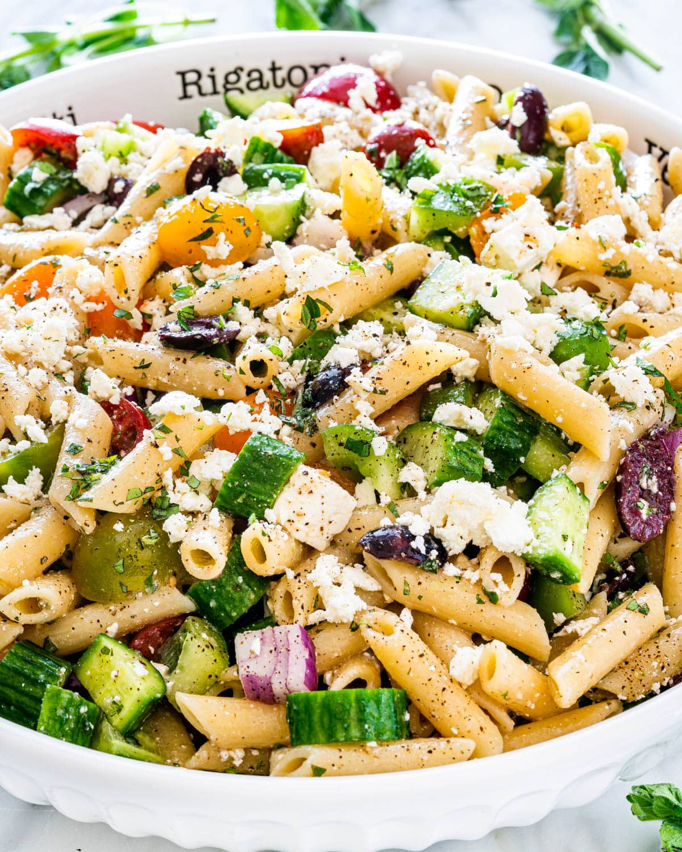 a large white bowl of greek pasta salad