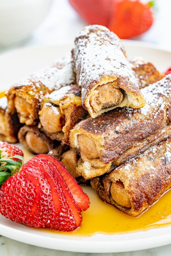 sausage french toast roll ups dusted with powdered sugar and topped with maple syrup - one has a bite taken from it, on a plate with whole sliced strawberries