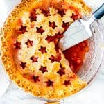overhead shot of a strawberry rhubarb pie with two slices missing and a pie lifter sitting in the empty space