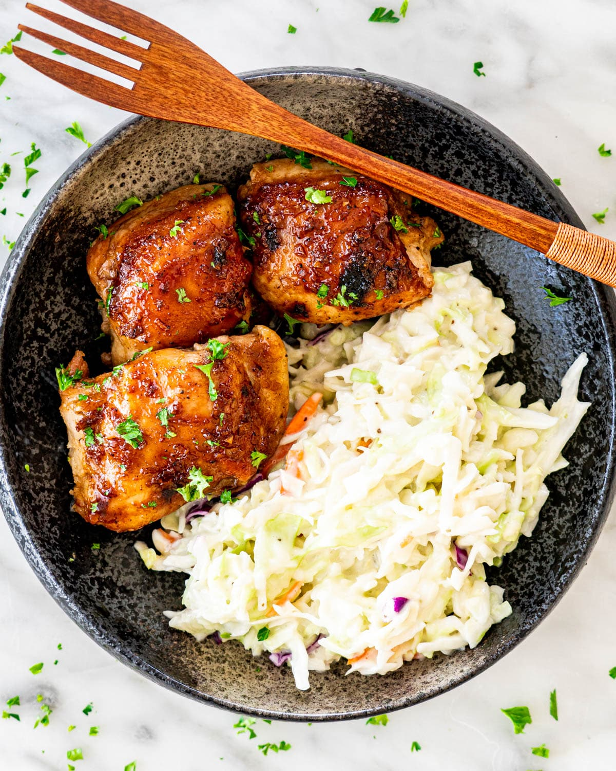 overhead shot of baked chicken thighs and coleslaw in a black dish