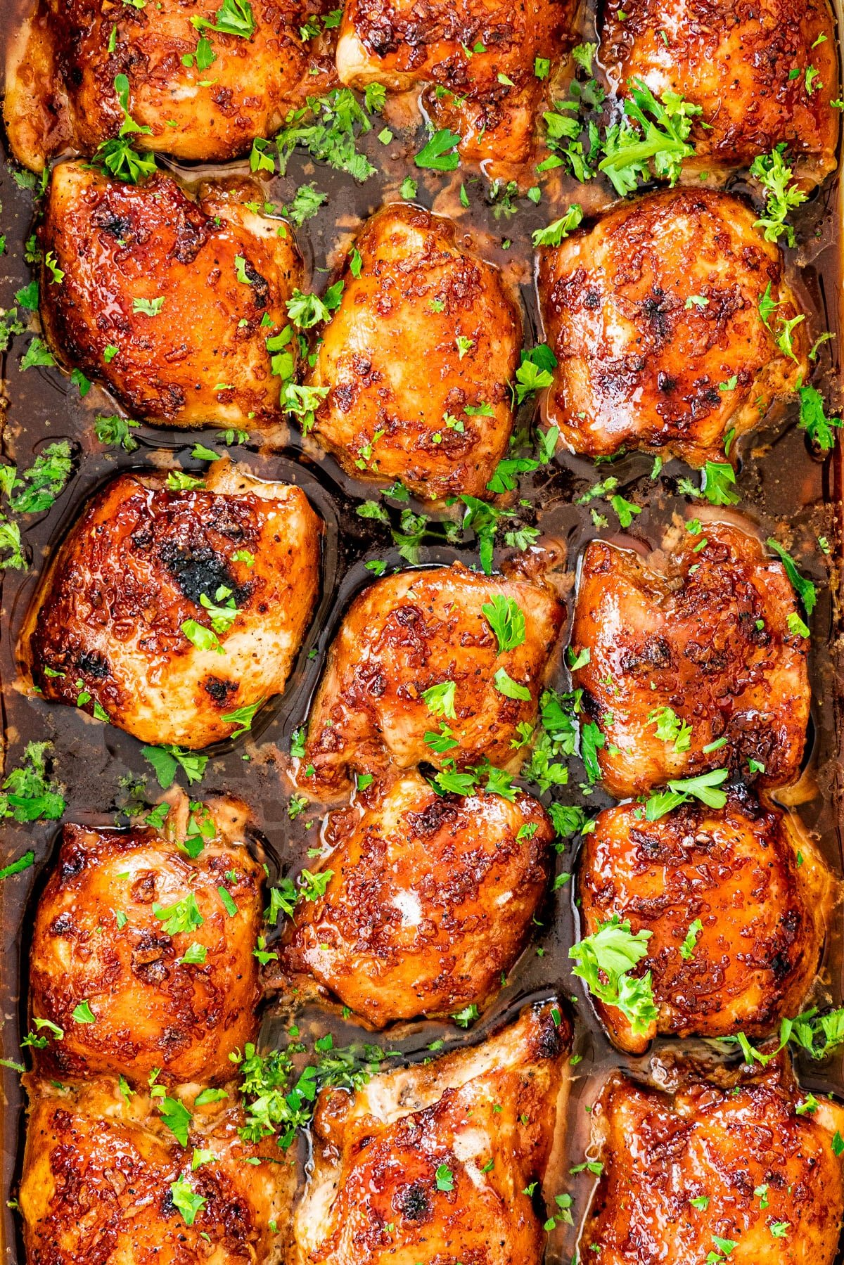 overhead shots of Brown Sugar Garlic Chicken thighs in a casserole dish garnished with parsley