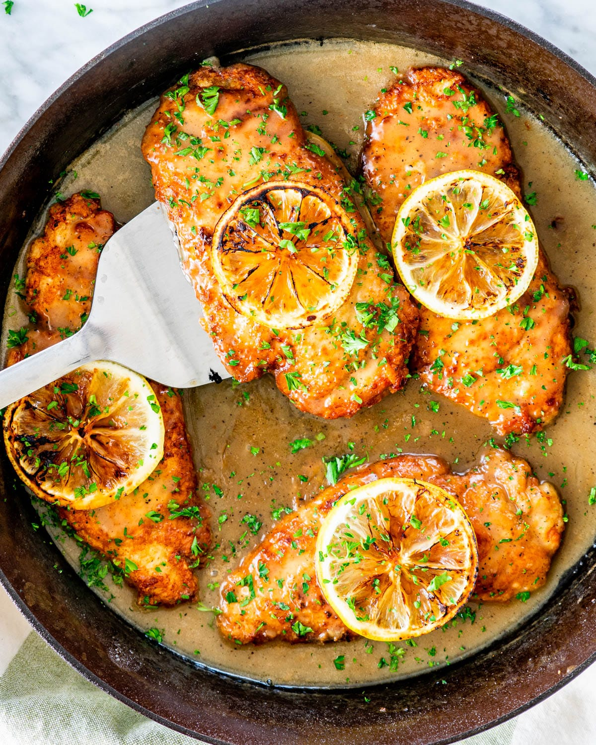 overhead of chicken francese in a skillet