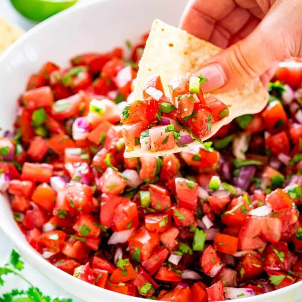 a hand taking a scoop of pico de gallo with a tortilla chip