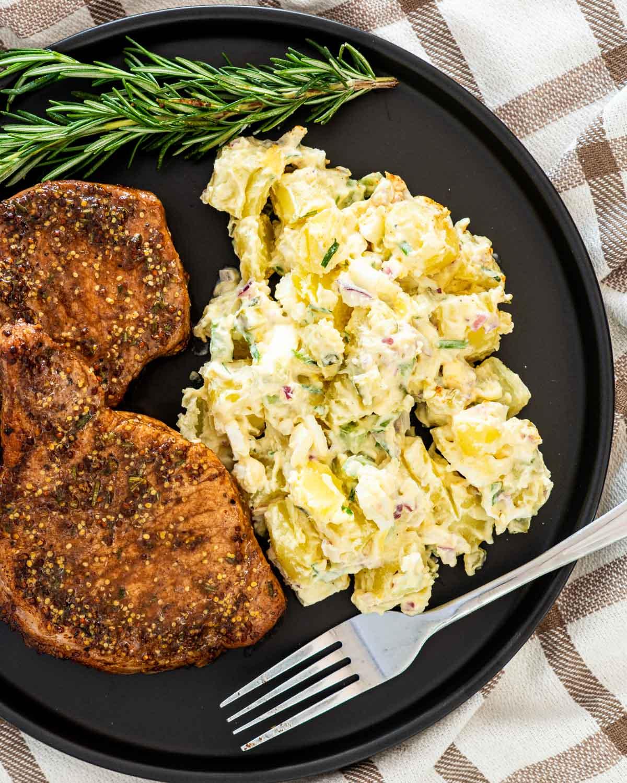a mustard balsamic pork chop on a black plate sliced up next to potato salad.