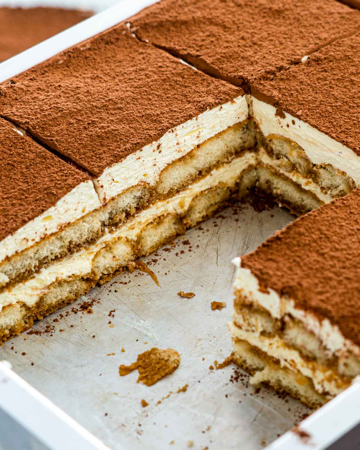 tiramisu in a pan with some slices taken out.