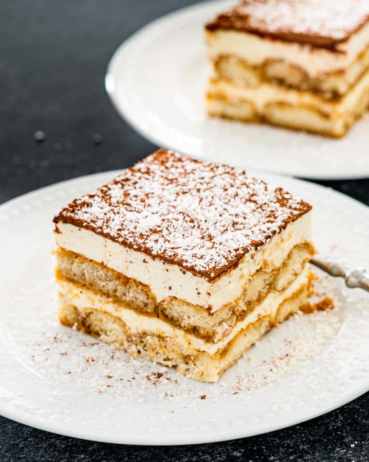 a beautiful slice of tiramisu on a white plate garnished with some shaved chocolate.