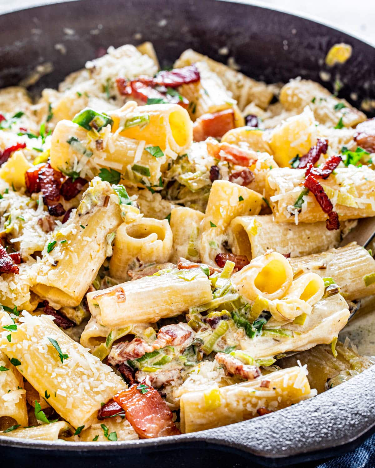 rigatoni in a creamy bacon and leek sauce in a black skillet