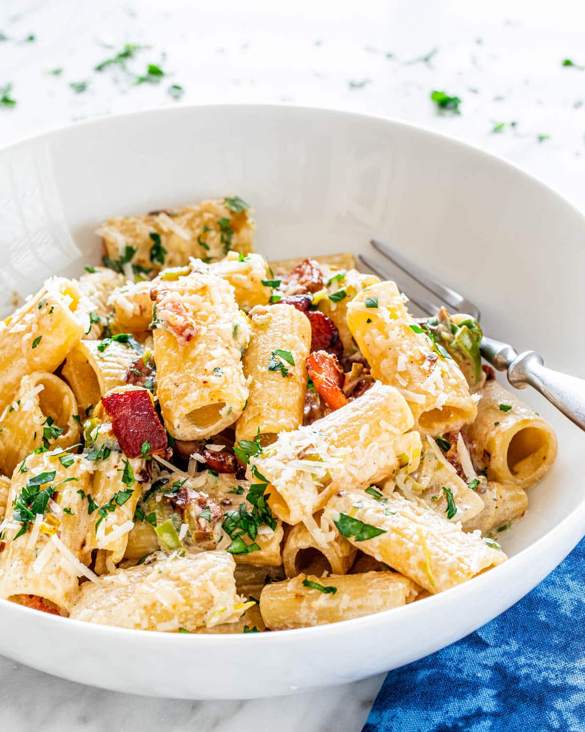 a white bowl holding a plate of rigatoni with creamy bacon and leek sauce