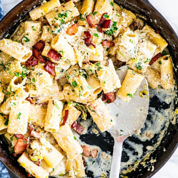 overhead shot of bacon leek pasta in a skillet with a serving spoon in it