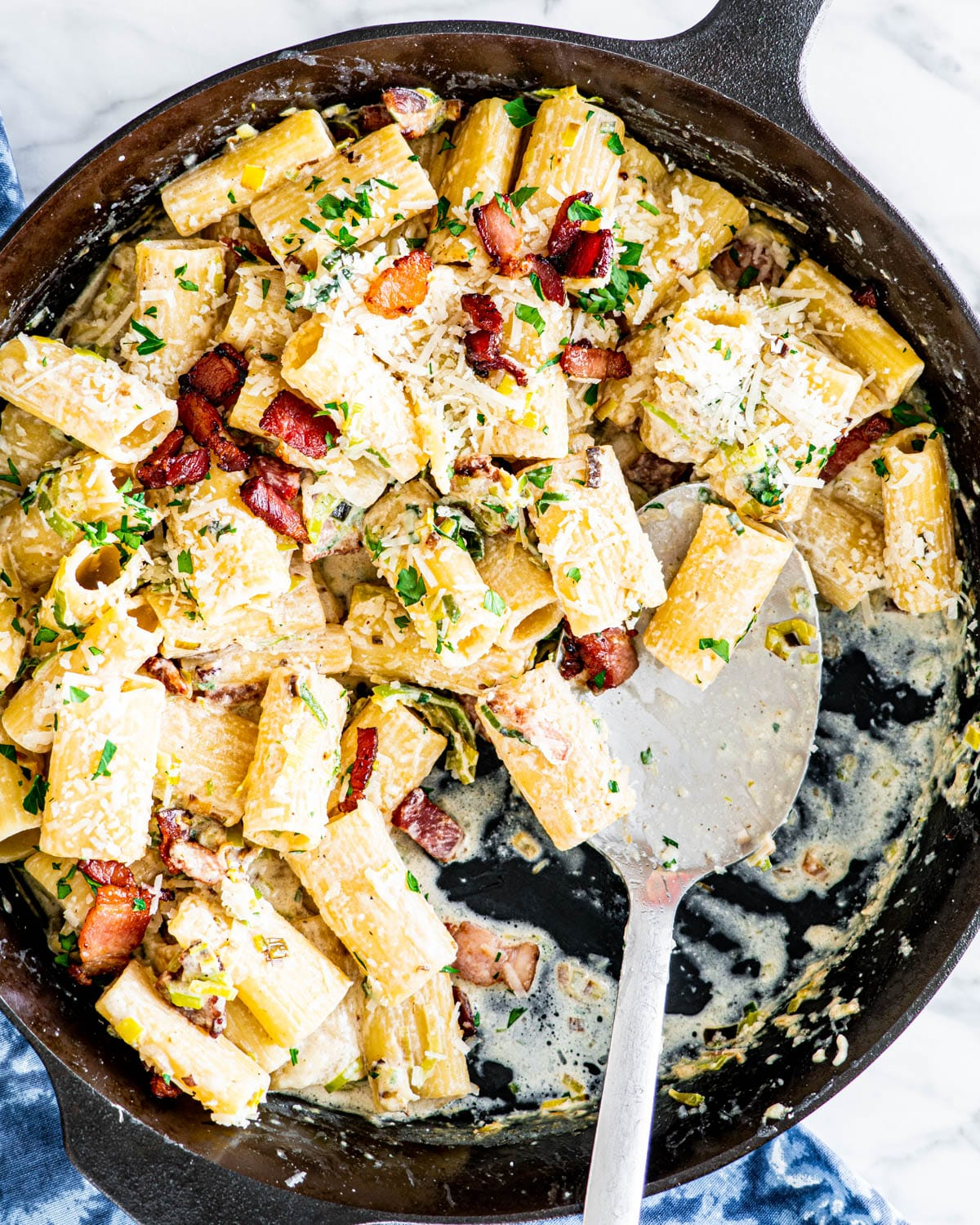 overhead shot of bacon leek pasta in a large black skillet