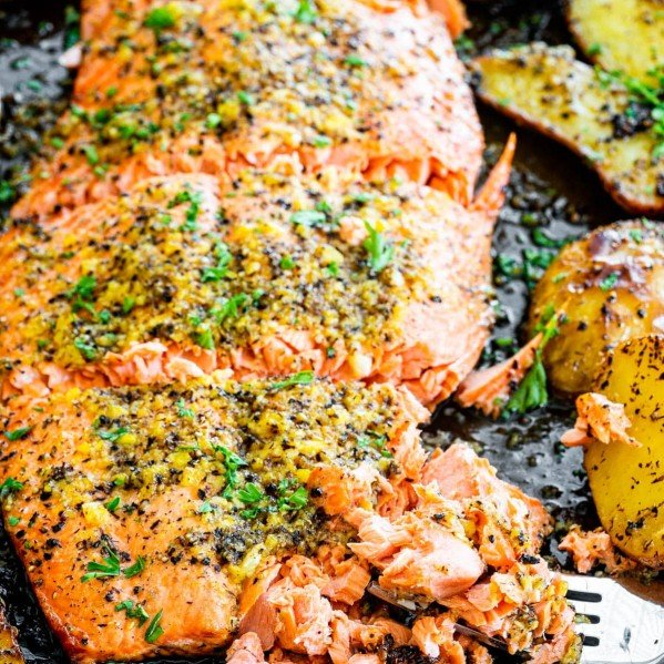 baked lemon pepper salmon with a piece being flaked by a fork