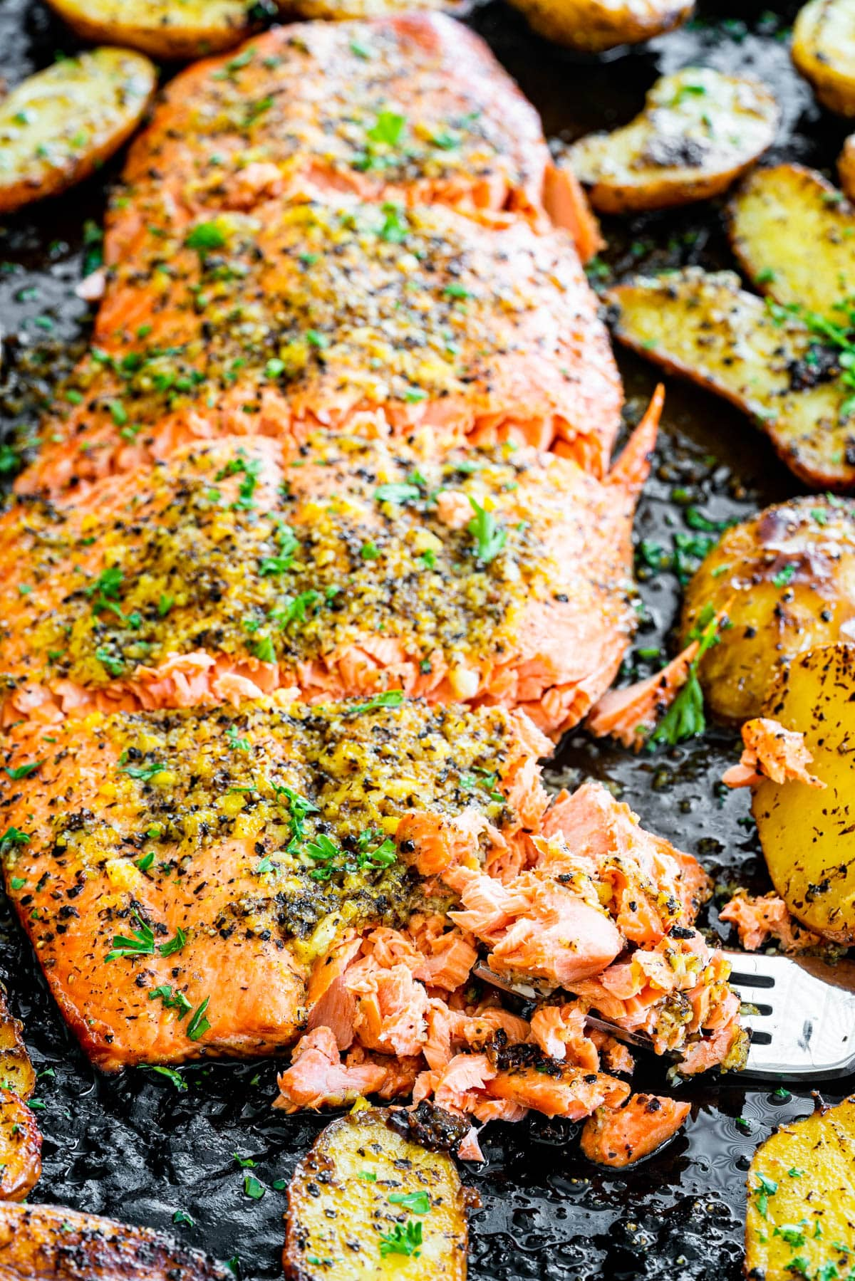 lemon pepper salmon cut into 4 pieces on a baking sheet surrounded by potatoes