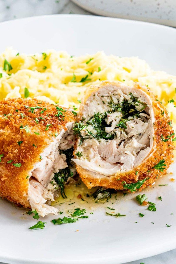 side view shot of chicken kiev on a plate with mashed potatoes