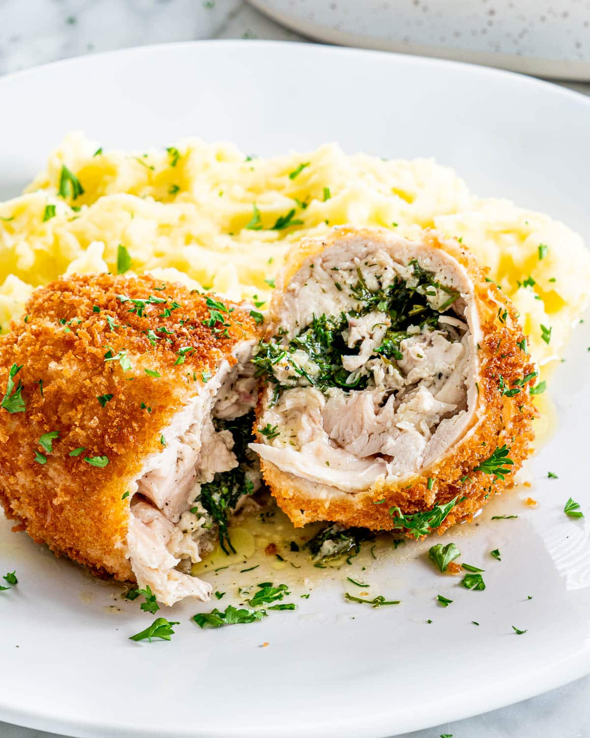 a plate of chicken kiev with mashed potatoes