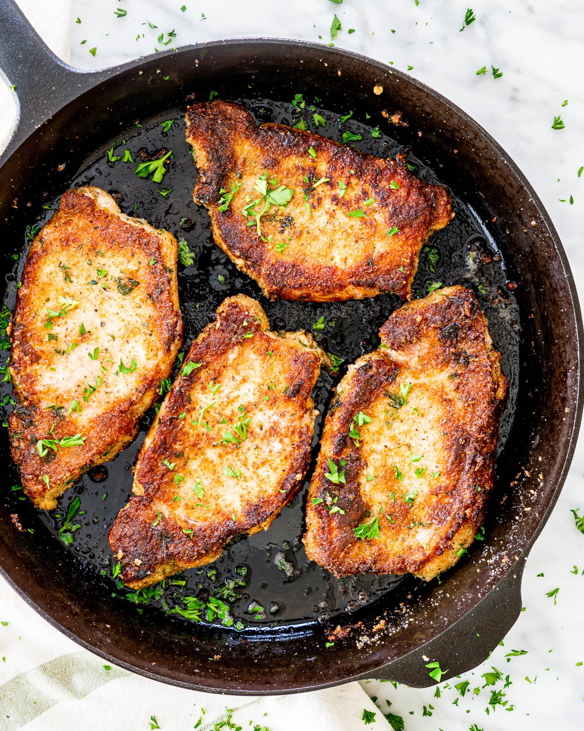 overhead shot of 4 italian pork chops in a skillet