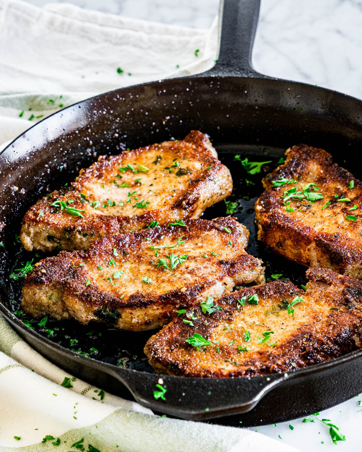 a skillet with 4 Italian Breaded Pork Chops and garnished with parsly