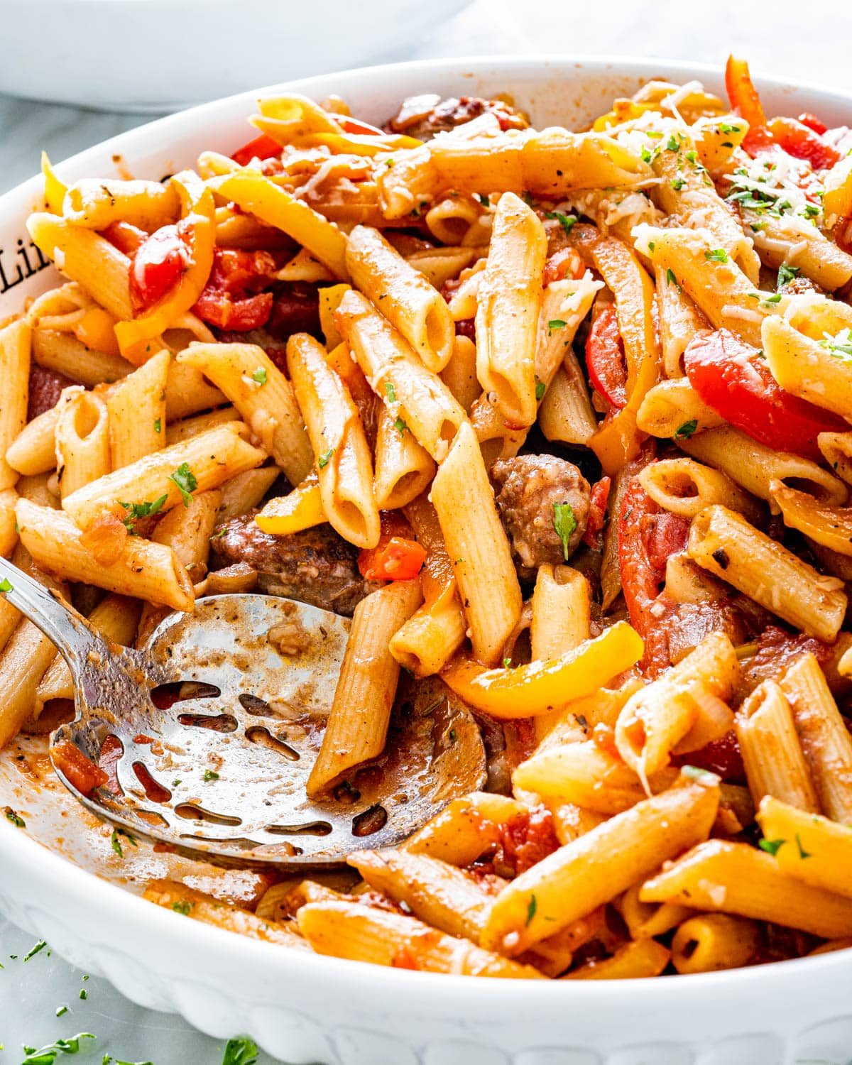 a large bowl loaded with Sausage Pepper Pasta with a serving spoon inside