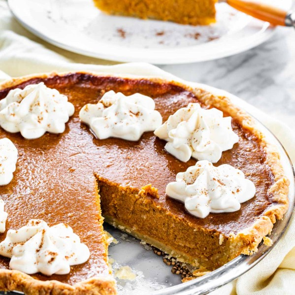 pumpkin pie topped with whipped cream with a slice on a plate in the background.