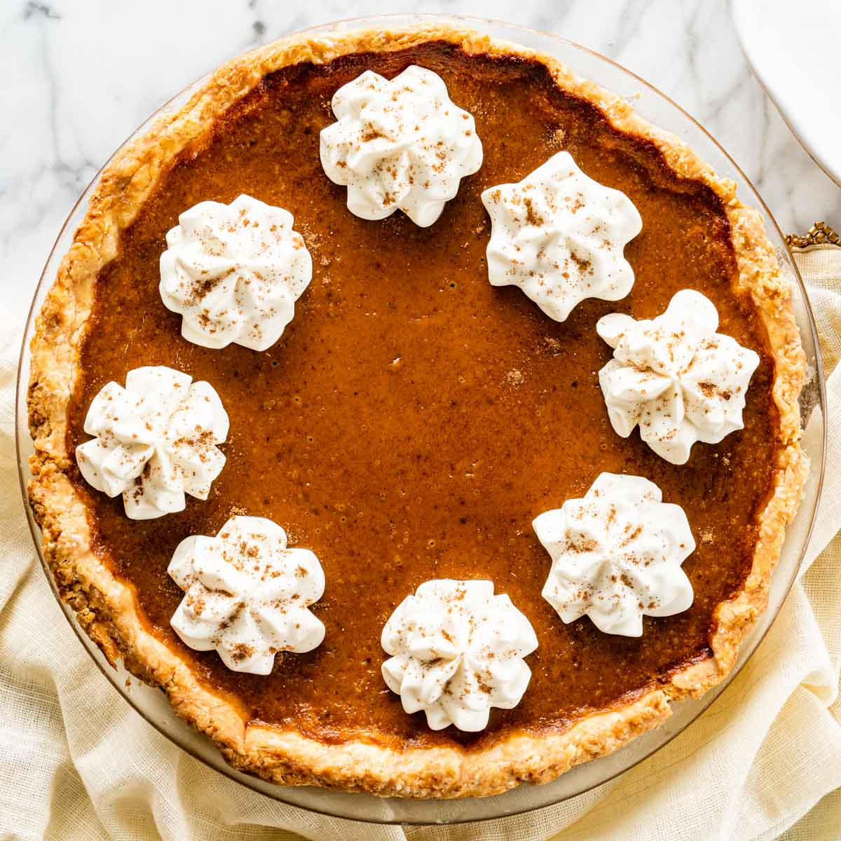 overhead shot of a freshly baked pumpkin pie with whipped cream topping.