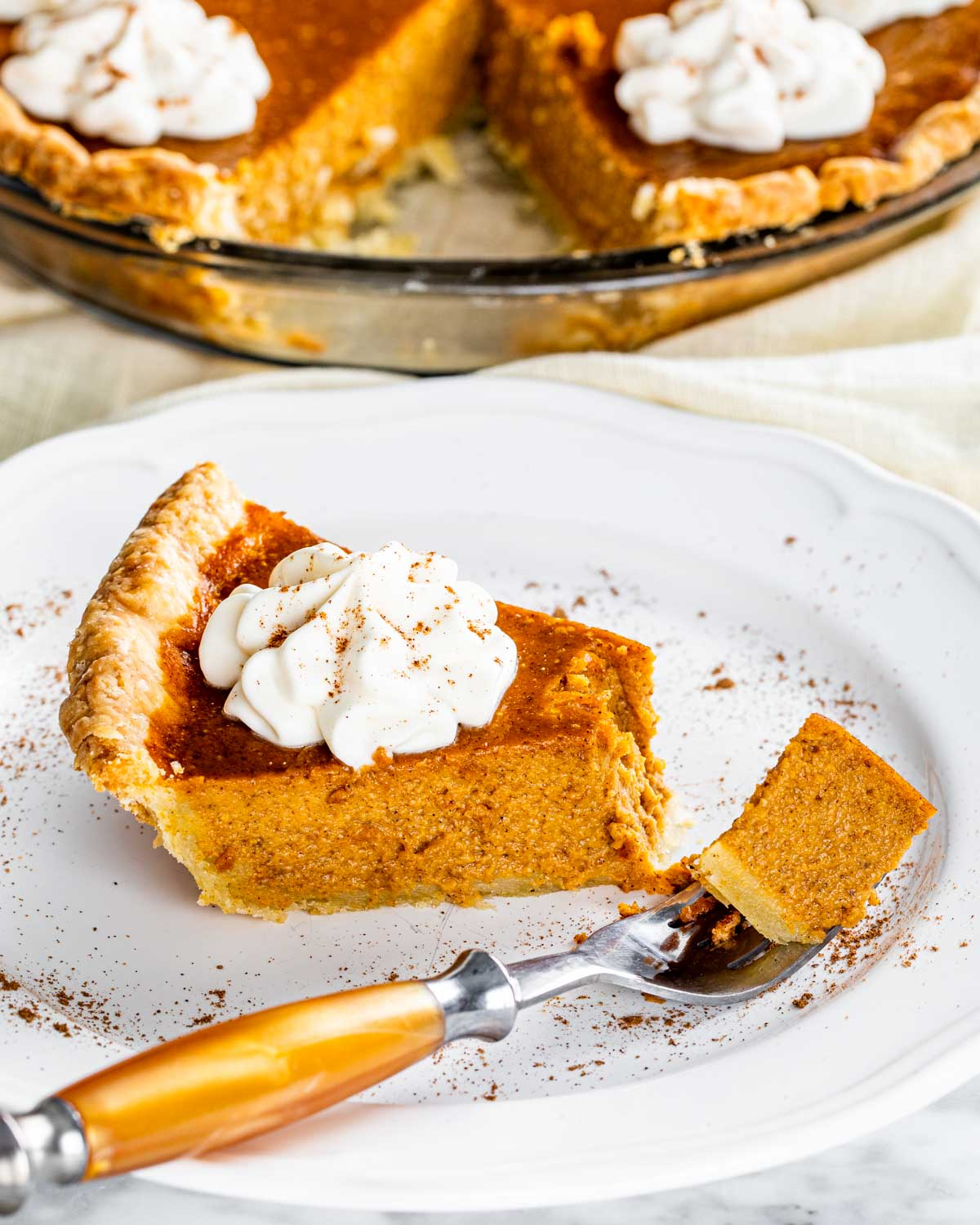 a slice of pumpkin pie on a white plate.