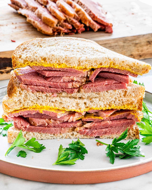 a corned beef sandwich with mustard, cut in half
